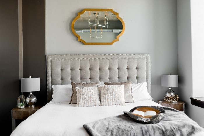 Gray and white bedroom with mirror over headboard